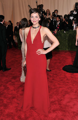 Maggie Gyllenhaal revealed some front and side cleavage in a red halter gown by Calvin Klein Collection. She accessorized with a Tod's clutch and Bulgari jewels.