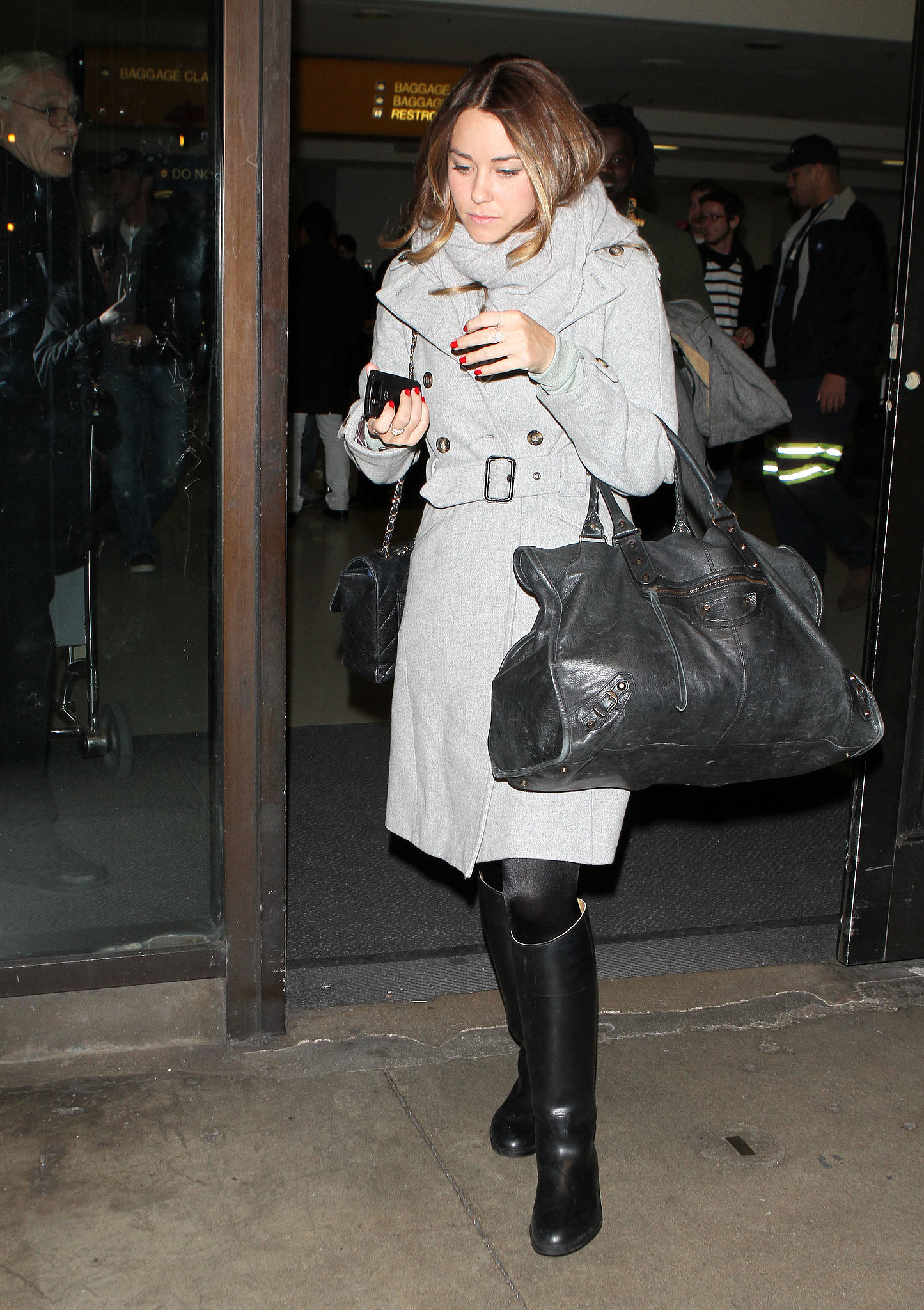 Lauren bundled up in a long gray trenchcoat, rain-proof boots, and an oversize Balenciaga bag at LAX. Lesson from Lauren: it's all about layers for a fashionable and functional travel style.