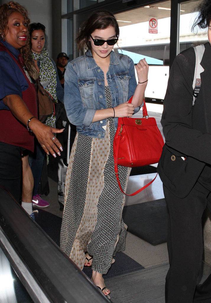 Hailee Steinfeld created the perfect Summer travel ensemble in her denim jacket, printed maxi dress, Ray-Ban Wayfarers, a bright red bag, and black patent flip-flops.