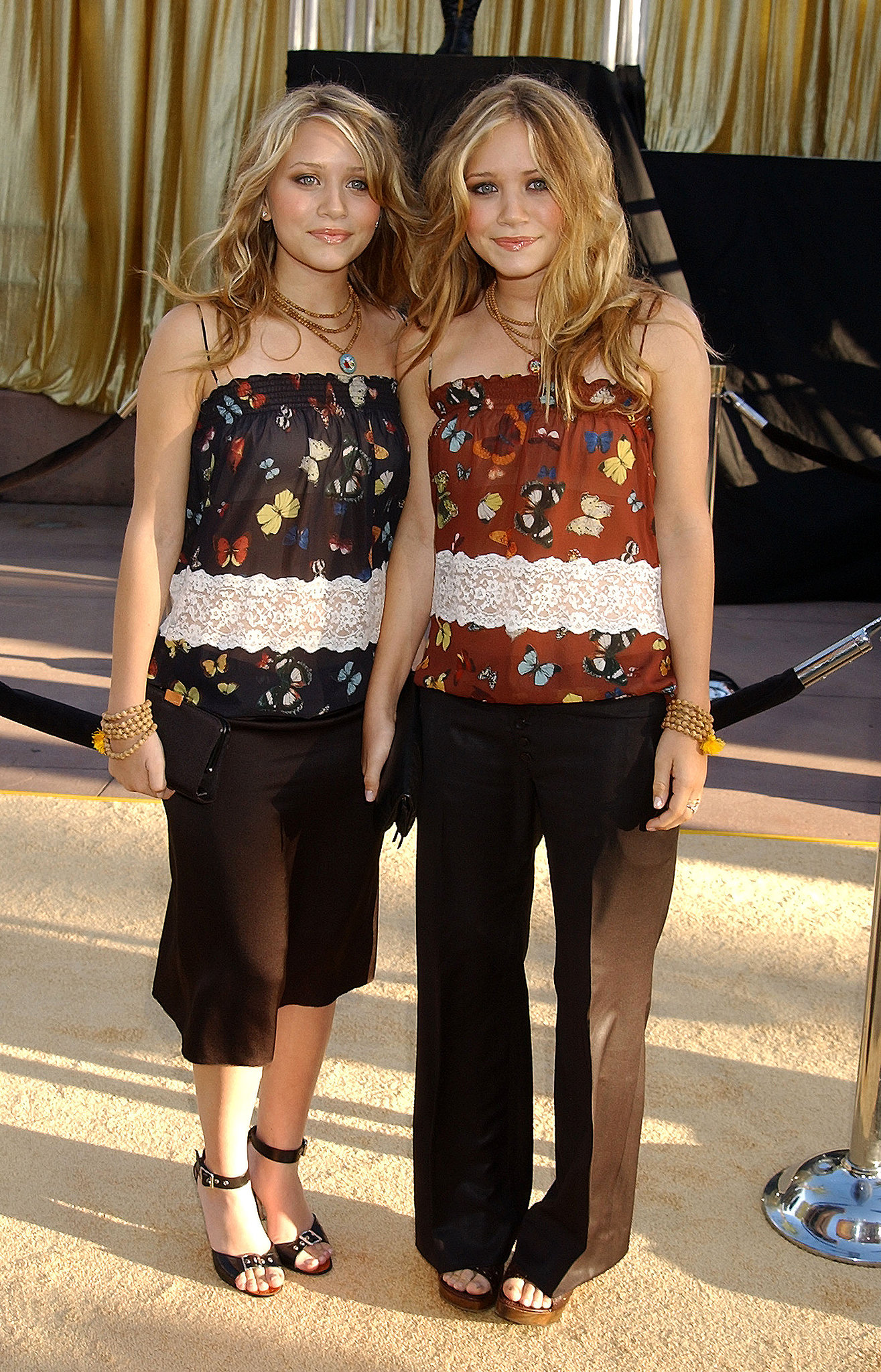 Twinning combo: For the 2002 LA premiere of Austin Powers in Goldmember, the Cali-cool combo styled their coordinating butterfly-print tops with black basics.  Ashley stuck with a dark palette, pairing her printed top with cropped black pants and buckle-accented sandals. Mary-Kate injected a pop of color via a burnt-orange blouse and a few beaded accessories.