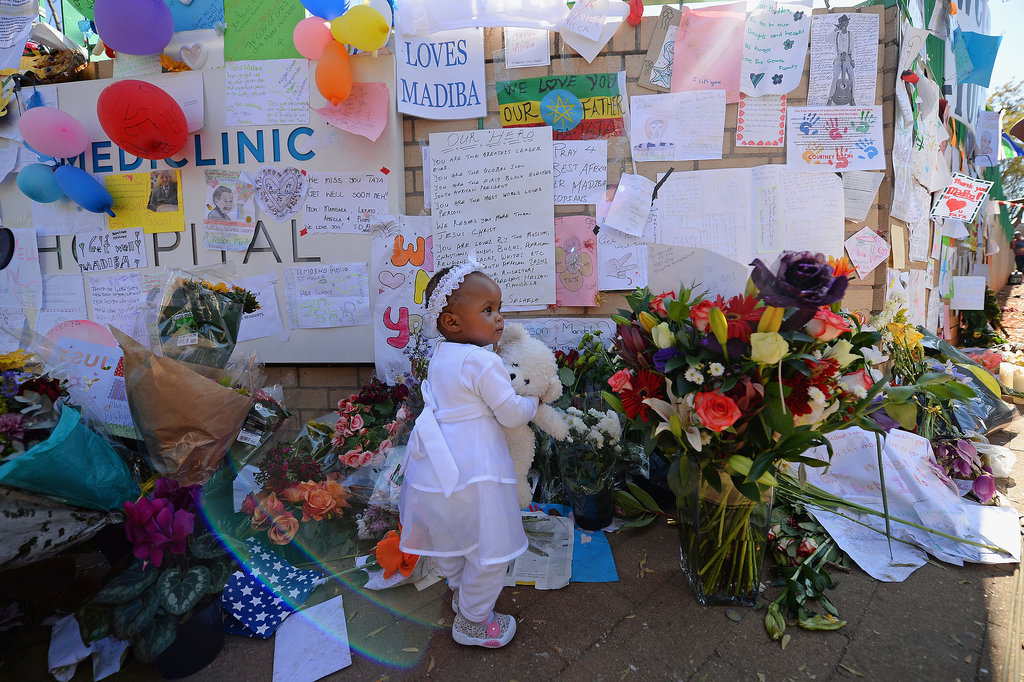 A little girl added a teddy bear to the wall lined with tributes, gifts, and flowers.