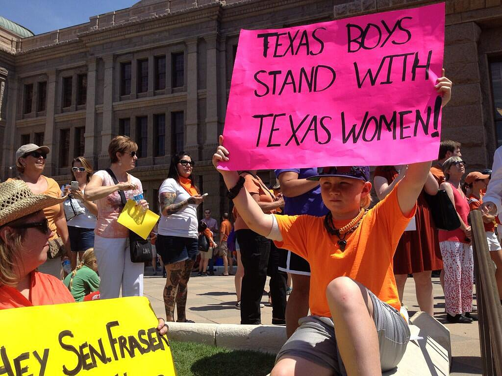 A young boy held up a poster during the protest. Source: Twitter user dallasdemocrats