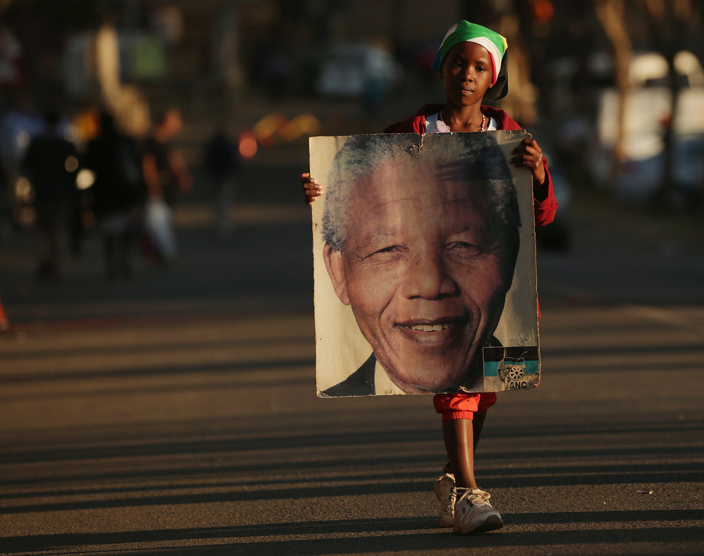 A child carried a picture of Mandela to add to the memorial wall outside the hospital.