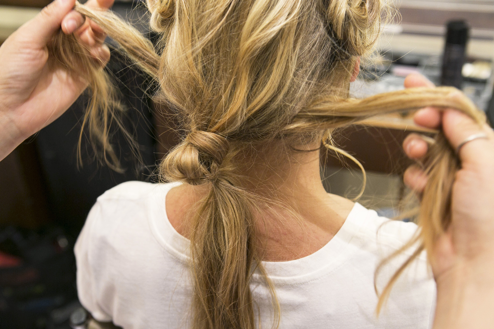 Now that you have the top of your look finished, it's time to revisit the loose ponytail and the hair along your neck. Split the loose hair underneath the ponytail into two even sections as shown here.