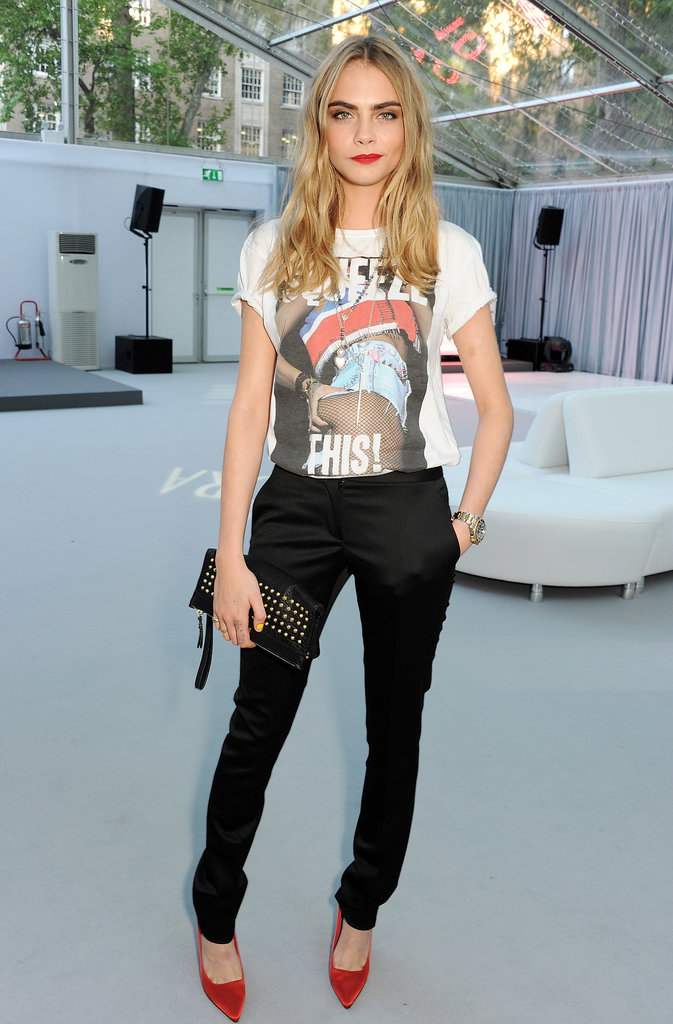 Proof that Cara's eventwear has just as much personality as her street style: a cheeky tee, trousers, and red pumps.