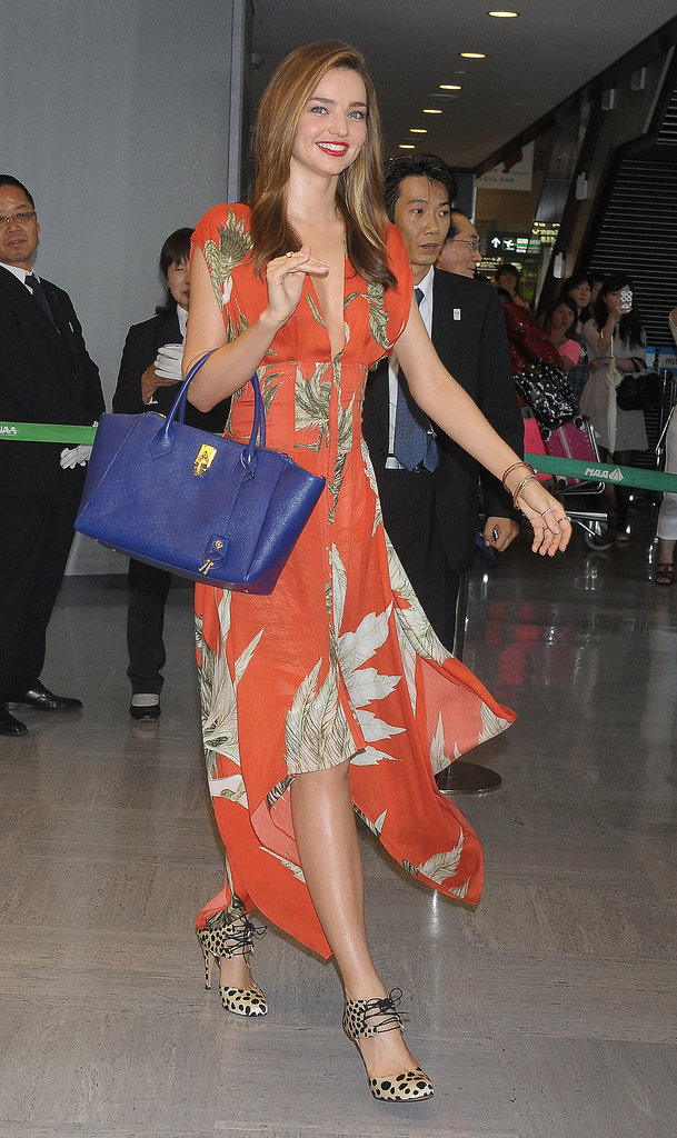 Leave it to Miranda Kerr to look so chic while traveling. The model showed off an orange printed Wes Gordon maxi dress, leopard Bionda Castana heels, and a blue bag upon her arrival to Japan.