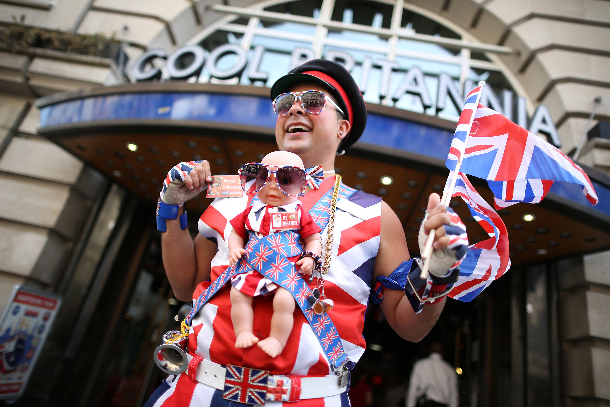 One man waved a flag in London's Piccadilly Circus to celebrate — with a fake baby attached to his chest.