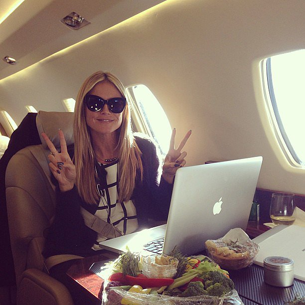 Heidi Klum flashed double peace signs during a flight to NYC. S
