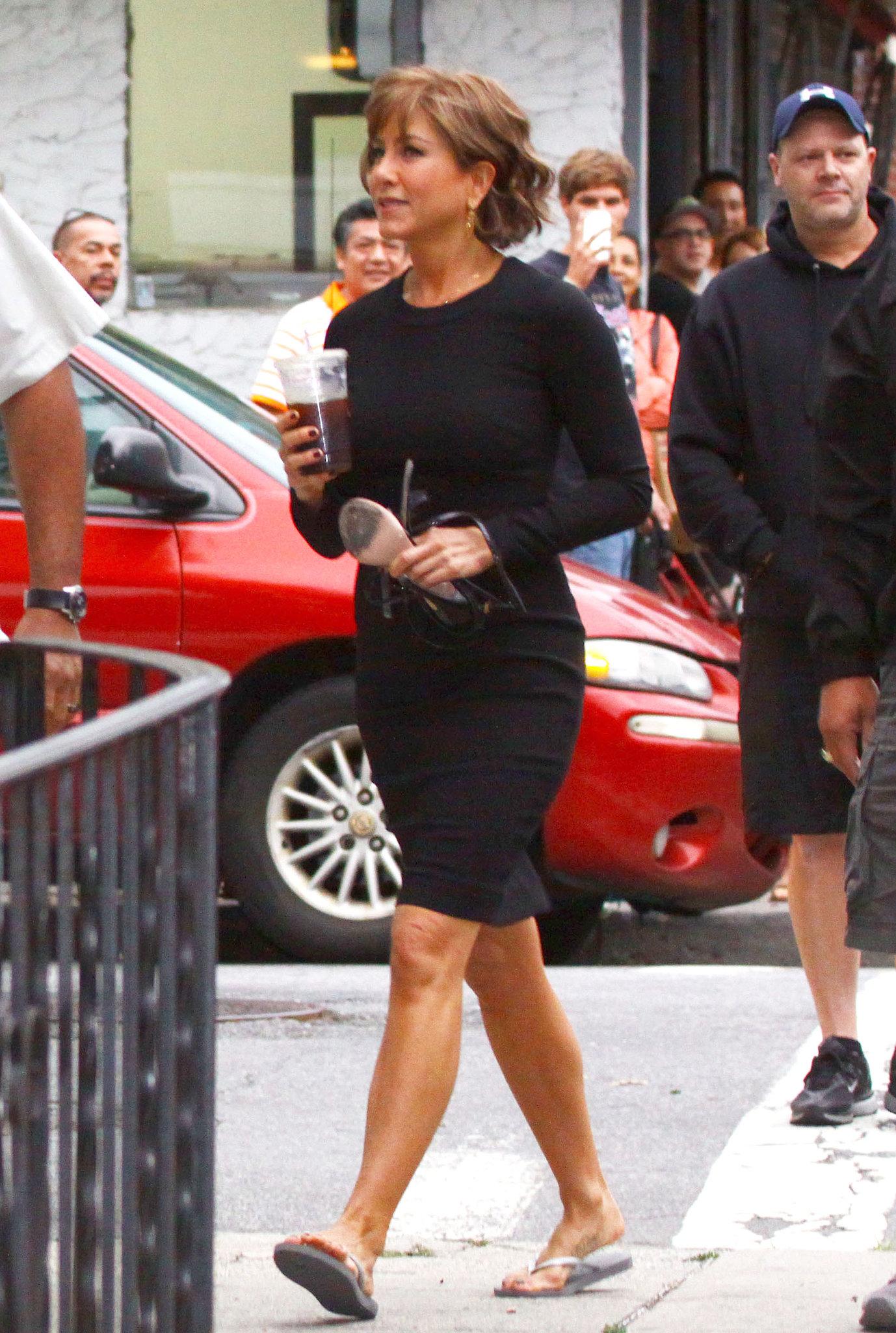 On July 25, Jennifer Aniston carried her heels while walking in more feet-friendly flip-flops.