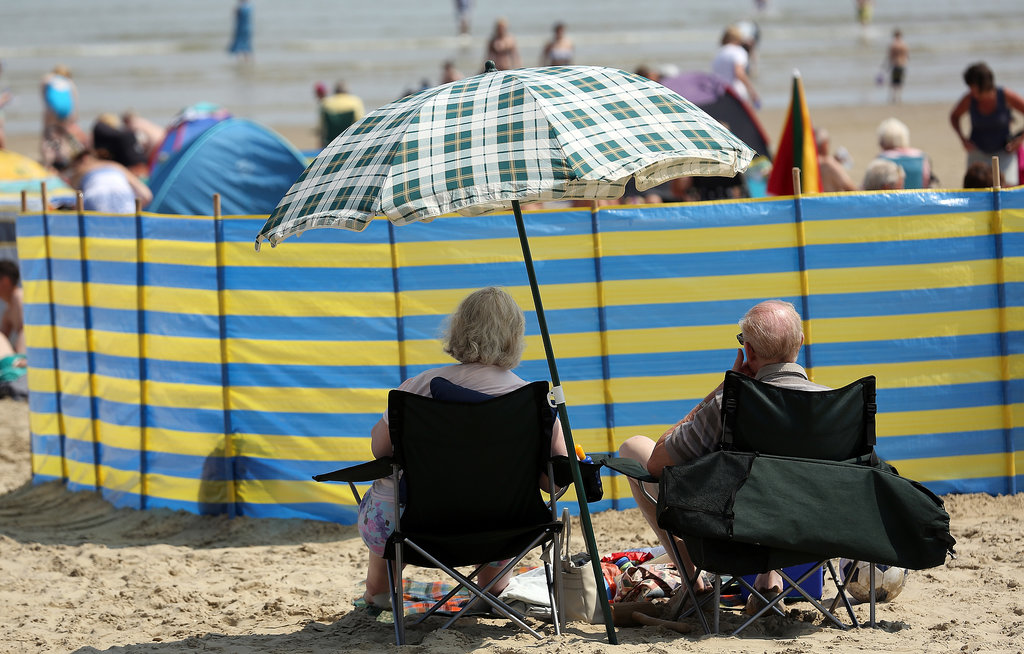 In the UK, a couple took shelter under an umbrella.
