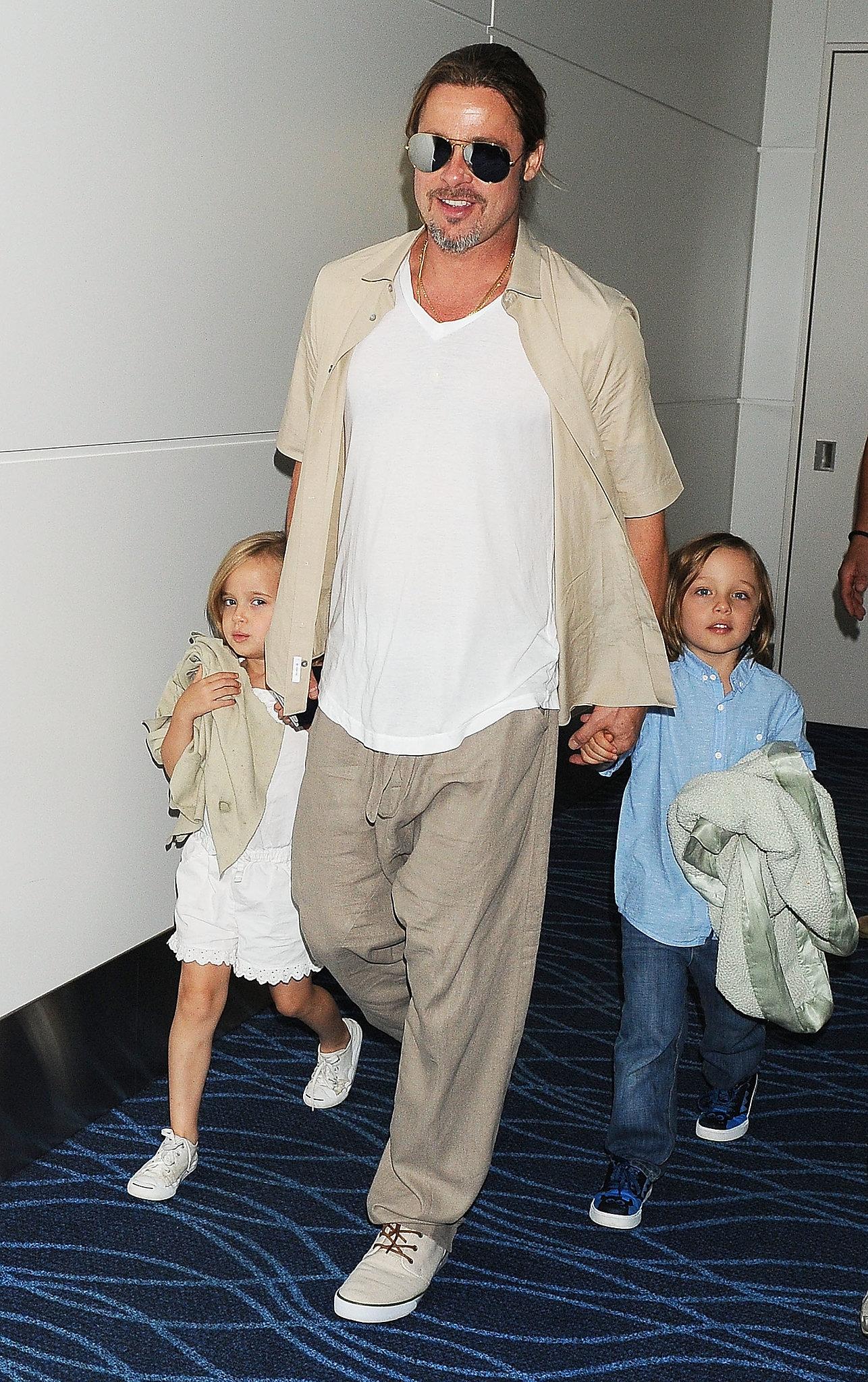 Brad Pitt smiled while walking with his kids.