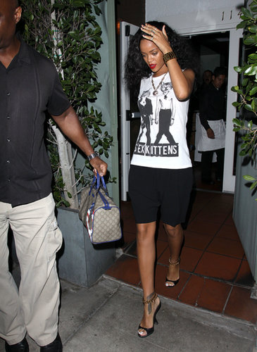 Rihanna was snapped heading out of an LA restaurant in 2012 wearing a sassy sex kittens tee by Corner Shop with black shorts, chain-strap sandals, and a Gucci satchel.