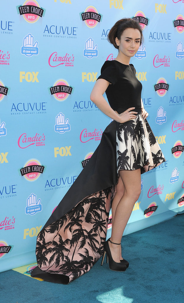 Lily Collins flaunted her gams in ankle-strap Brian Atwood platforms, a playful Fausto Puglisi palm tree skirt, and a black crepe Houghton top!