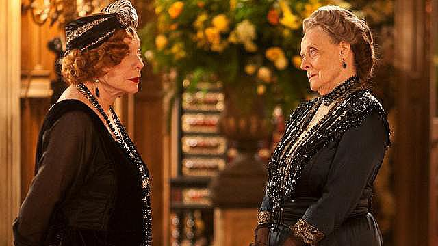 The addition of Cora's mother, Martha Levinson, to the cast in season three created a clash of sorts. The Dowager Countess of Grantham represents the classic Edwardian age (think: Gibson Girls), while the visiting matriarch embraces a more non-traditional persona (think: Louise Brooks). As you can see, Martha (left) doesn't shy away from loads of accessories and a bit of lip rouge.
