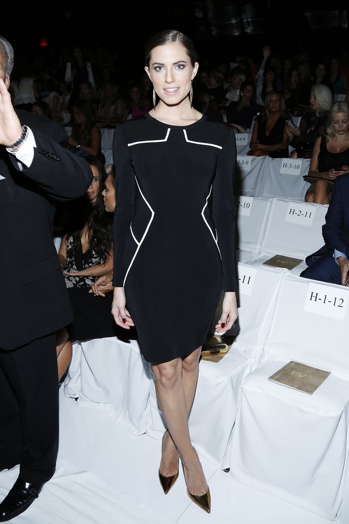 Allison Williams looked sleek in a black dress with white piping at the Diane von Furstenberg show. She finished with gold drop earrings and gold metallic pumps.