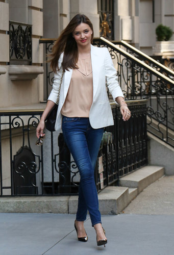En route to the US Open, Miranda Kerr managed to make basics look anything but boring. She paired a nude silky top with skinny jeans from Frame Denim, then added a crisp white blazer, pointy pumps, and a chain-handle bag.