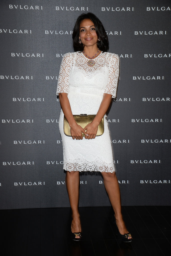 Rosario Dawson dressed in a white lace dress, accented via a gold clutch, at the Bulgaro accessories collection event.