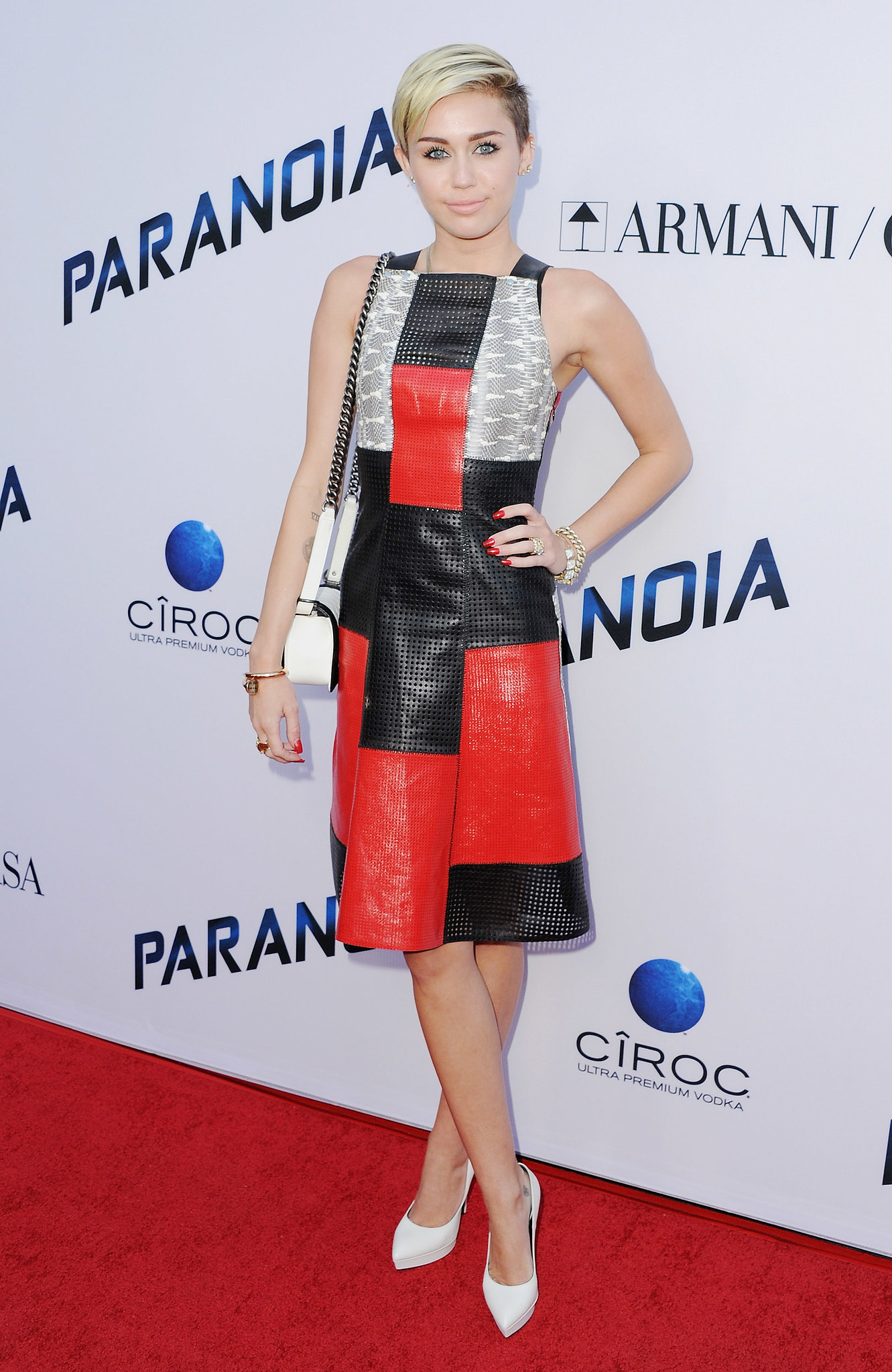 Cyrus stayed true to her signature color palette — red, black, and white — in a patchwork Proenza Schouler dress accessorized with a Chanel bag, Cartier nail bracelet, and white pumps at the LA premiere of Paranoia.