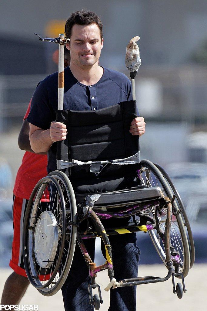 Jake Johnson carried a wheelchair on the beach.