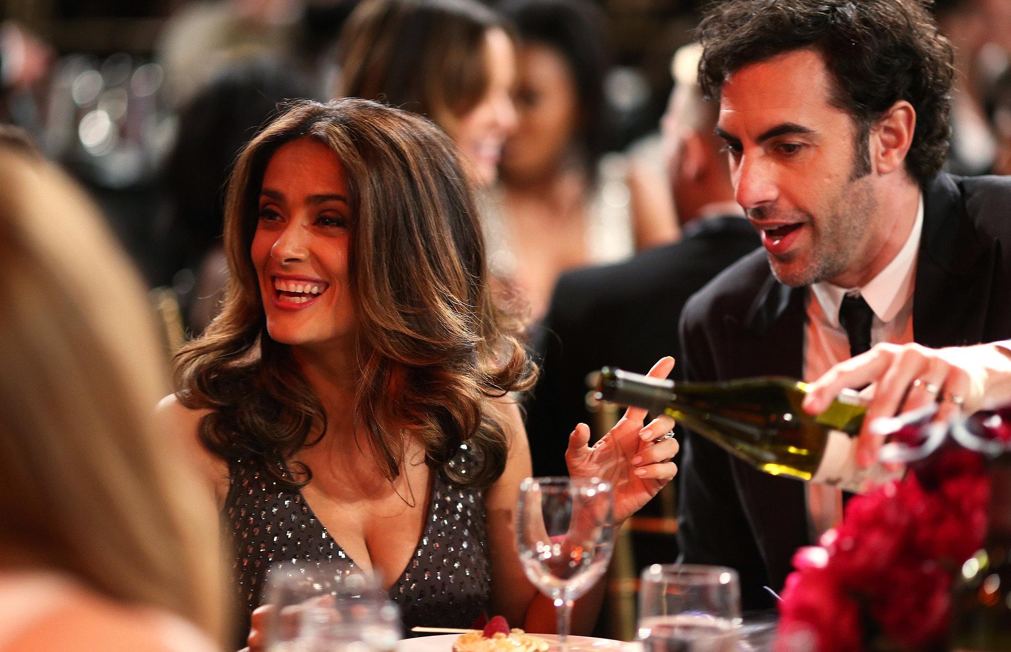 Sacha Baron Cohen poured Salma Hayek a glass of wine.
