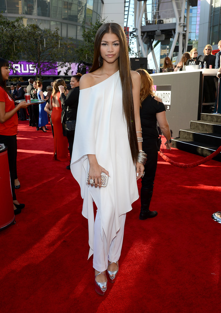 Zendaya looked pristine in an off-the-shoulder, fluttering white tunic and coordinating trousers from Donna Karan's Resort 2014 collection, with mirrored sandals. The Disney star accessorized with an embellished Swarovski clutch, shimmering bangles, and white nail polish.