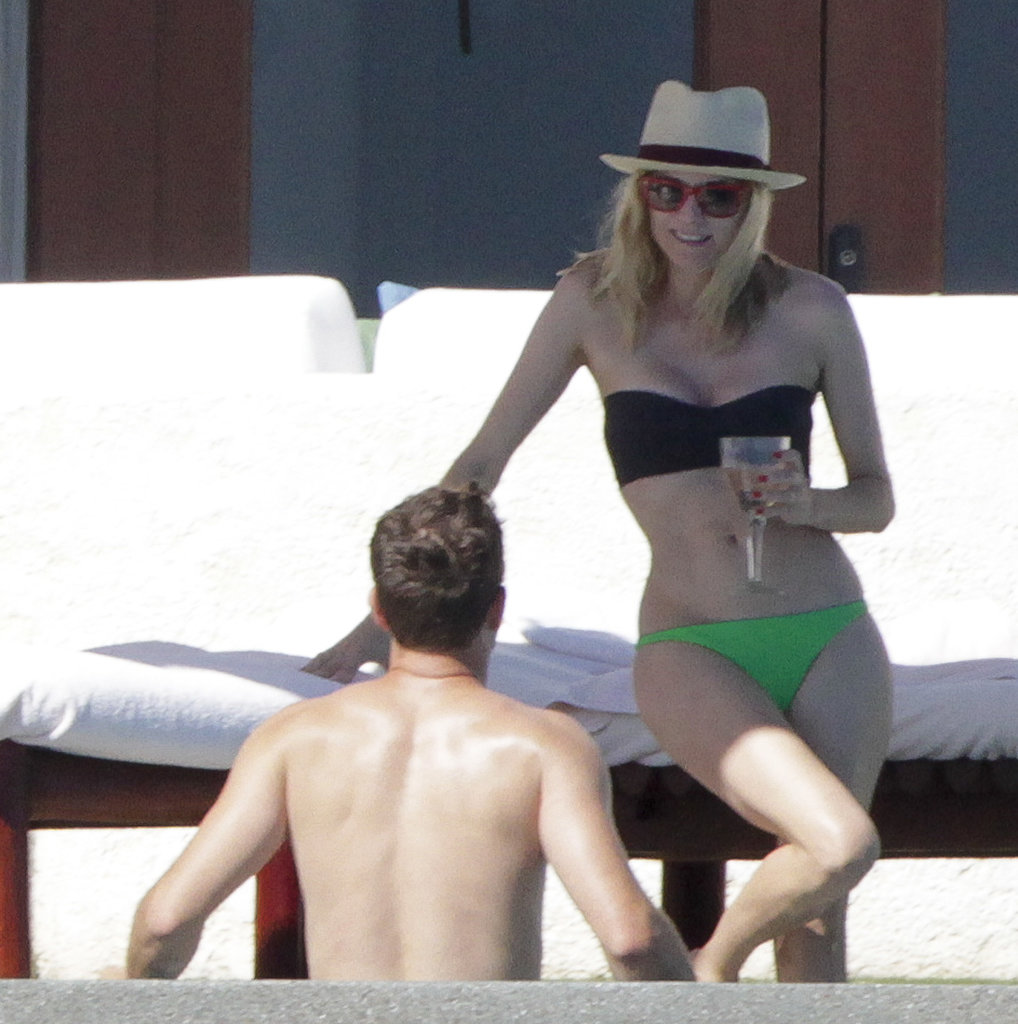 Diane Kruger relaxed by the pool with a glass of wine in a black and green set in Los Cabos, Mexico, in November 2013.