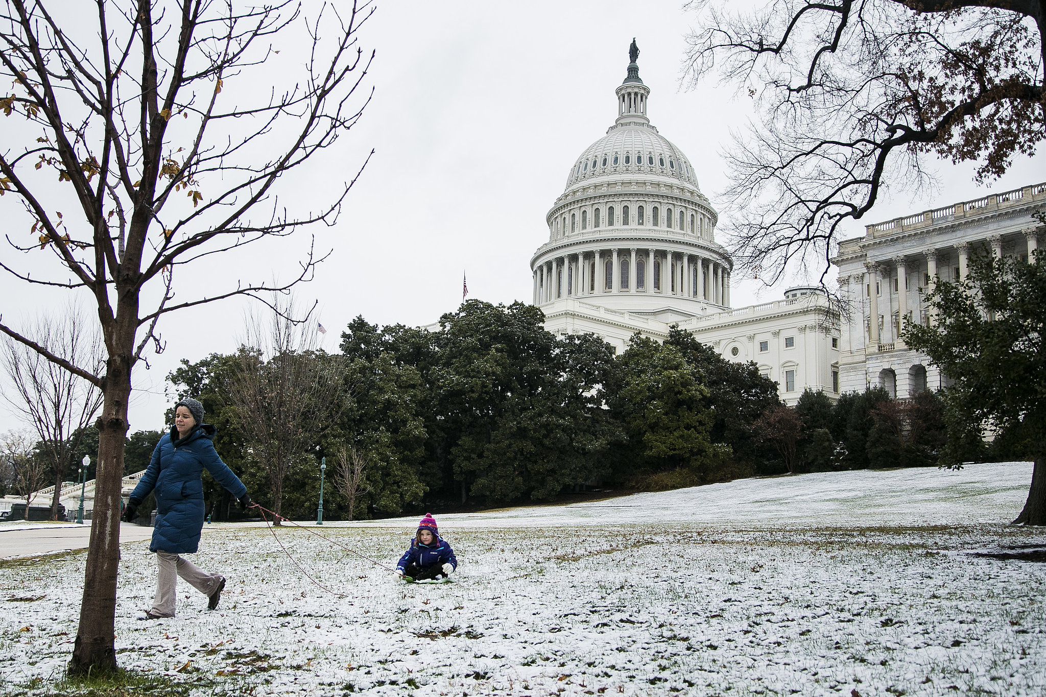 A woman pulled her daughter across snow-covered grass in Washington DC.