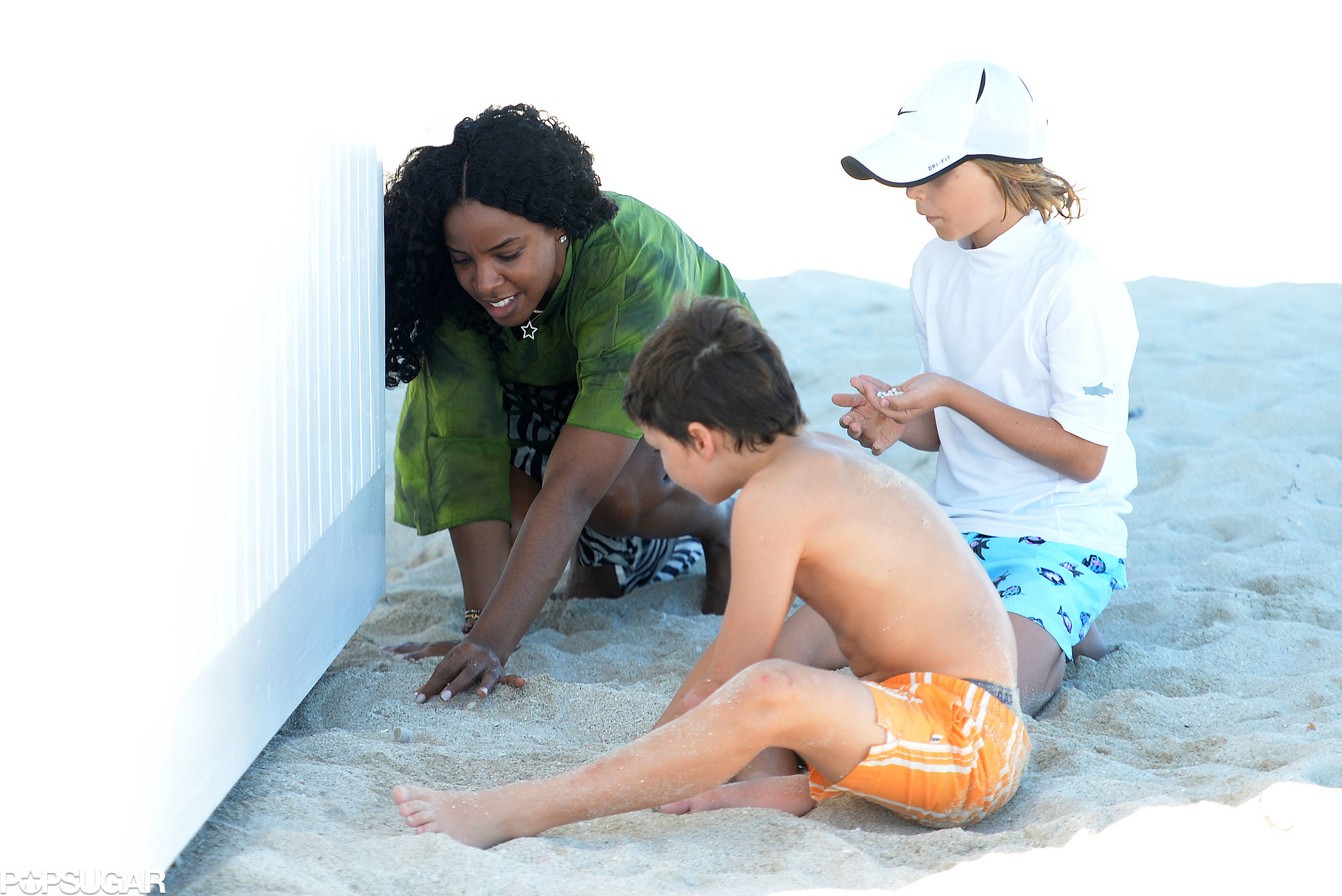 Kelly Rowland helped two kids build sand castles on the beach.