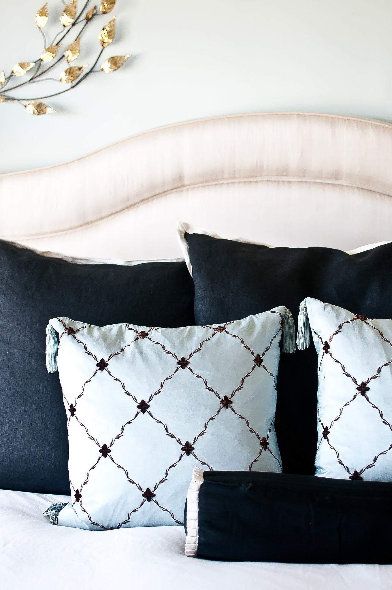 Black and powder-blue pillows contrast beautifully with the glamorous headboard in Lynn's bedroom. Source: Kassie Borreson