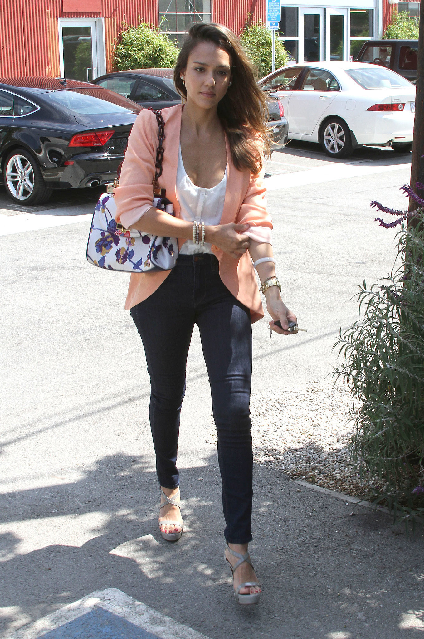 Jessica Alba took her LA basics — white Rails tank and dark blue denim — to new heights via a peach findersKEEPERS blazer and a floral Tory Burch bag.