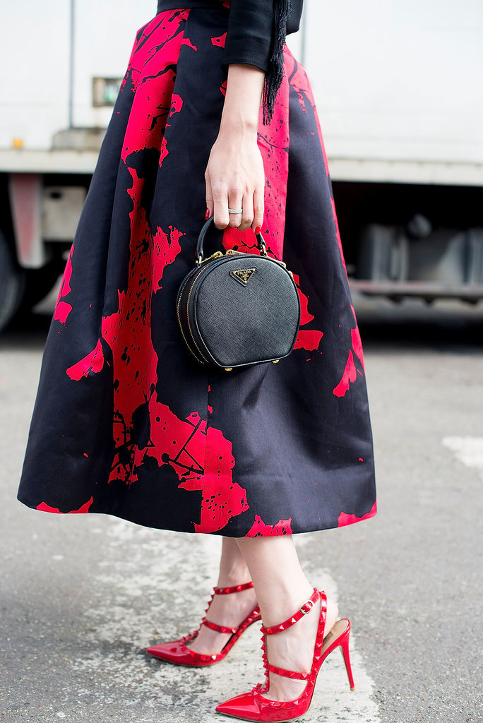 When you wear a ladylike skirt, like this one from Tibi, it's always wise to add ladylike accoutrements, like her top-handle Prada bag and Valentino heels.