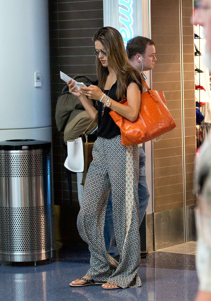Is this the most comfortable travel outfit in the world? Alessandra picked loose, flowy pants, sandals, and a black top for a trip to LAX.