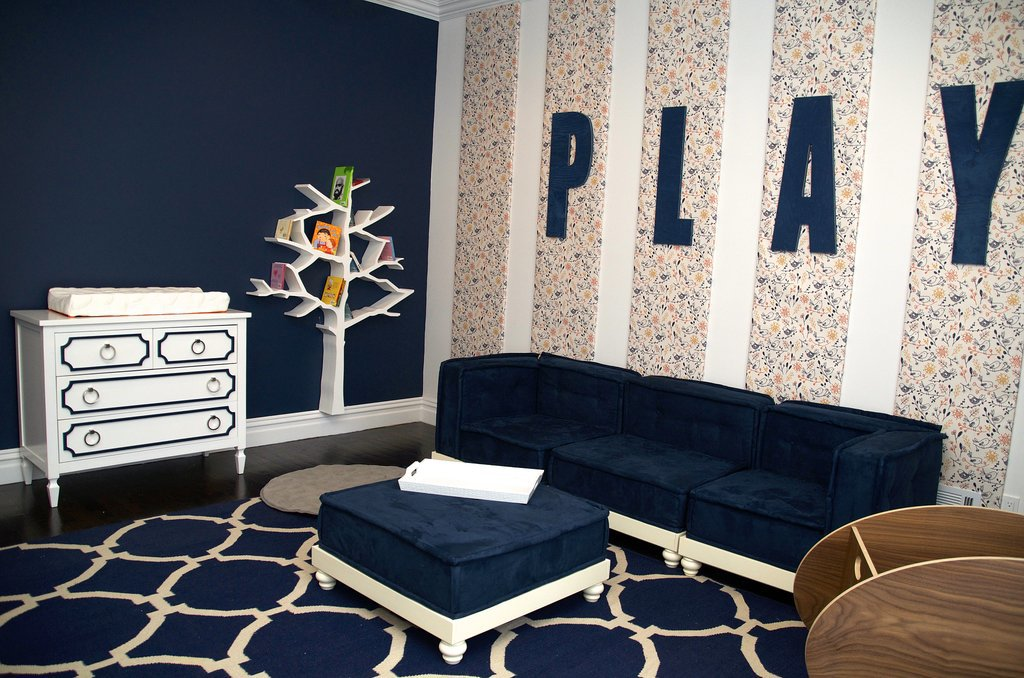 """PS: Vanessa, tell us about some of the individual pieces you incorporated into the room. VA: Each time I would pick a piece for the room, I'd say to myself, """"This is the focal item."""" Well, obviously everything can't be """"the item,"""" so here I have a room with [everything that I thought could be] a focal on its own, because they're all so perfect.  The Nurseryworks Tree Bookcase isn't only beautiful to look at — it's very functional. It holds more than 100 books. The Newport Cottages Beverly Changer brings a little glam into the room with its Hollywood Regency feel. The couch is from Pottery Barn Teen. It's low to the ground so that as Alena learns to walk and climb, it'll be safe and easy. Since Alena is too little to really play right now, I put a BabyHome So Ro Bassinet in the room so that Kevin and Danielle could immediately start spending time in there. The bird wallpaper took me forever to find, but when I finally did, I knew it was the one! It's by a company in Australia called Muffin & Mani. I expect many of their designs to turn up in my rooms from now on! The giant PLAY letters by Twelve Timbers make it very clear that a lot of fun is going to happen in this room! By mounting them on the wallpaper panels, it gave the room even more dimension. The area rug is by Jaipur, and in addition to being a perfect anchor for the space, it's very light and easy to roll up and take outside to shake out because we all know, messes happen. Source: Vanessa Antonelli for Nessa Lee Baby"""