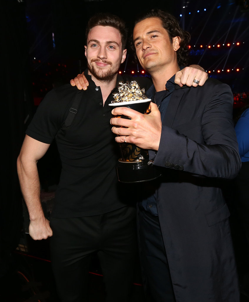 Orlando Bloom showed off his golden popcorn alongside Aaron Johnson.