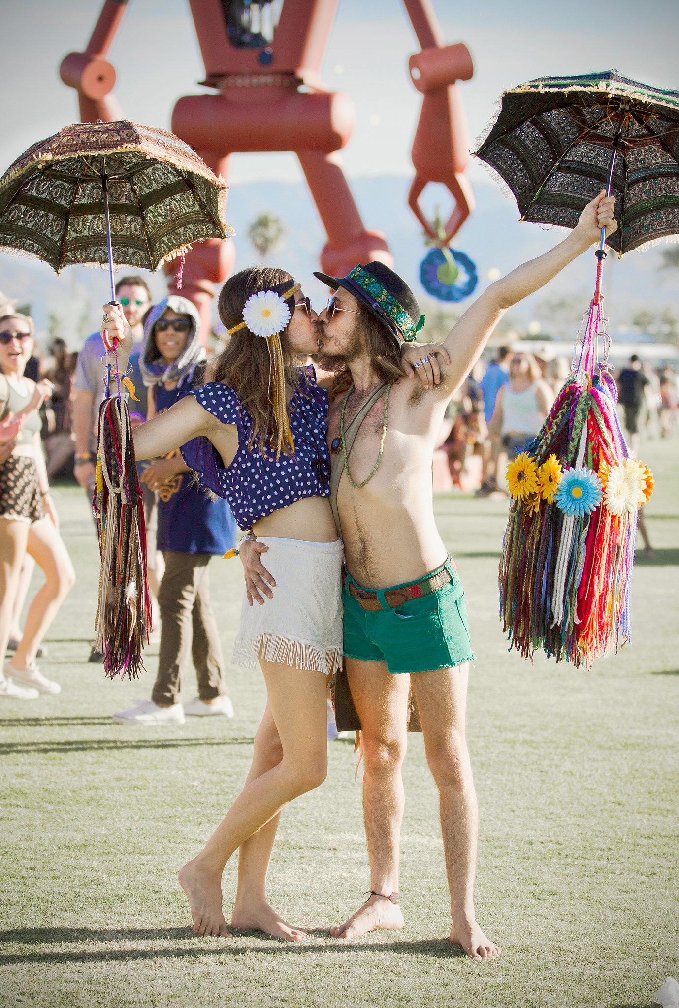 A Coachella couple kissed while holding umbrellas.