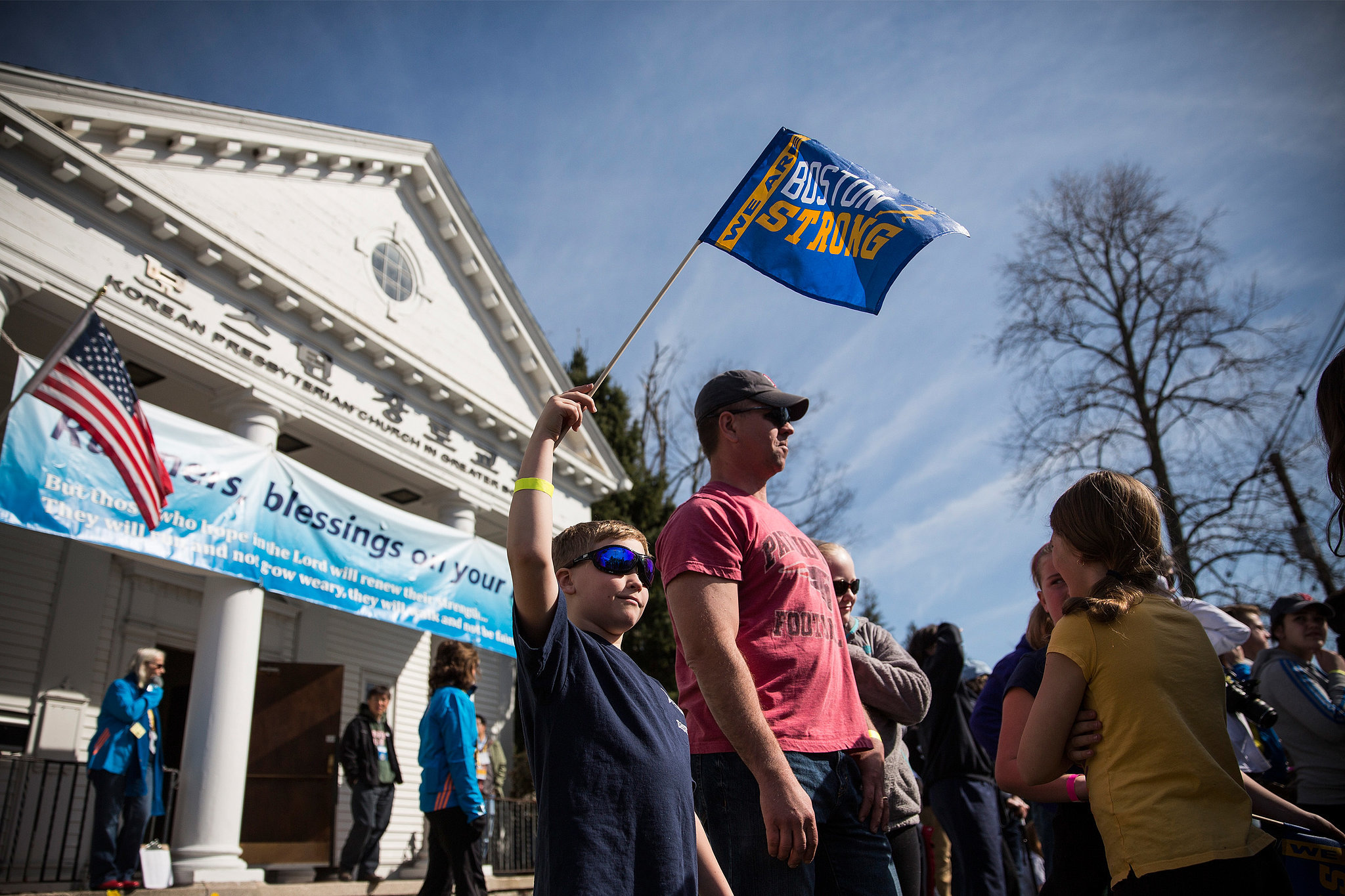 """An 8-year-old boy waved a """"Boston strong"""" flag."""