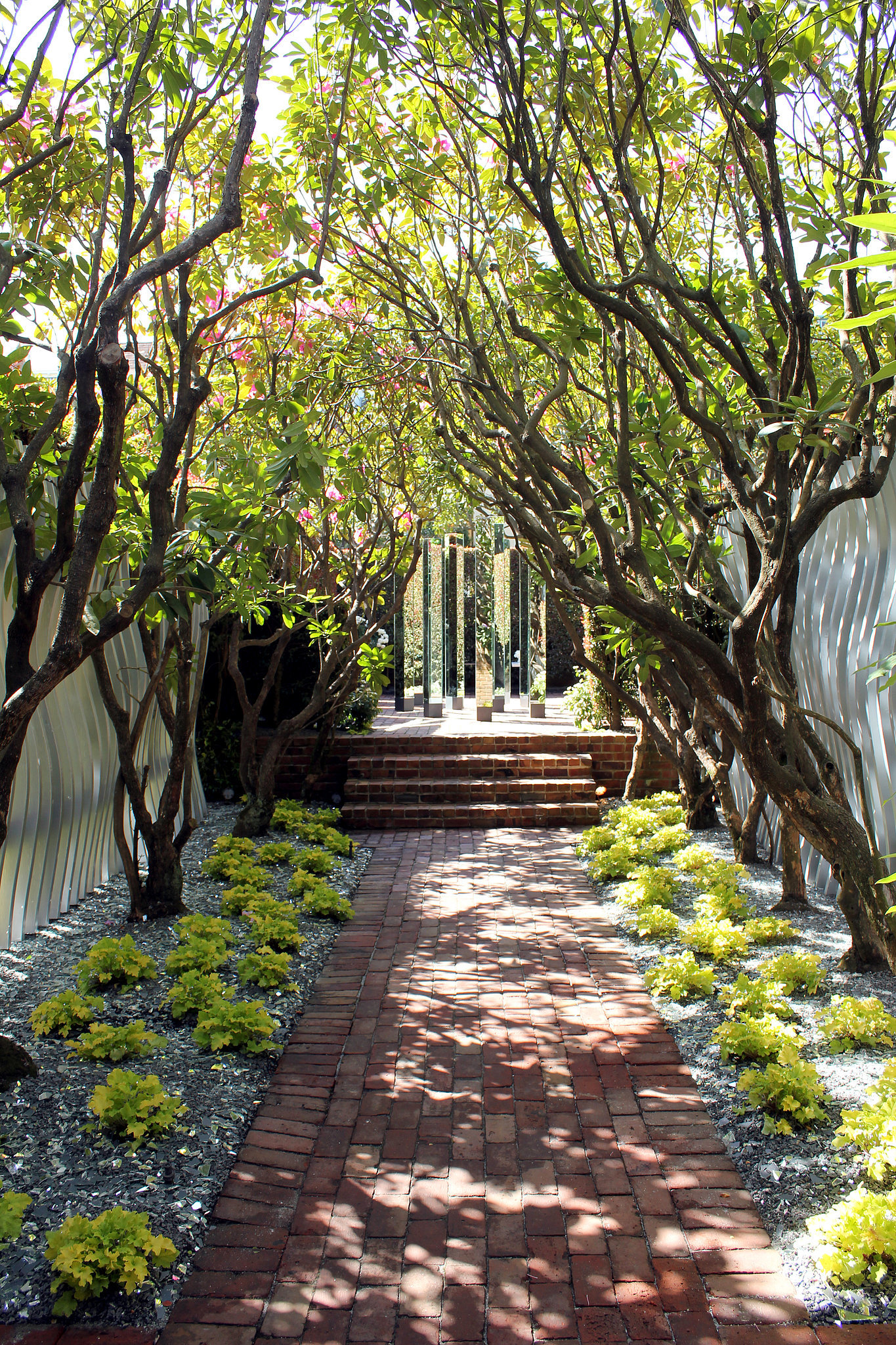 Here's something we hadn't thought of before: line the backyard walkway with shattered mirror pieces for a unique effect — and seal the deal with a mirrored sculpture at the end, just like Katharine Webster and Thayer Hopkins did for the showcase.