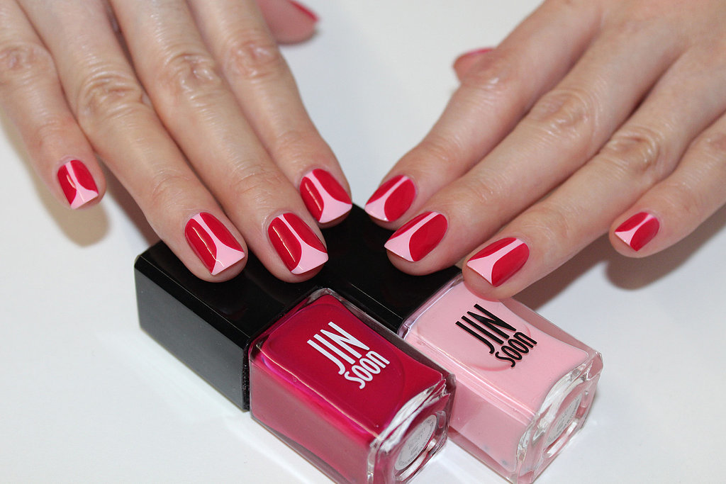 File and shape your nails to a natural square shape. Apply a base coat like Jin Soon Power Coat ($18). Apply Jin Soon Dolly Pink ($18) on the entire nail bed. With a thin brush, create the tulip petals with Jin Soon Cherry Berry ($18).  Starting at the cuticle area, draw a straight line down toward the tip of the nail, curving left three-fourths of the way down to cr