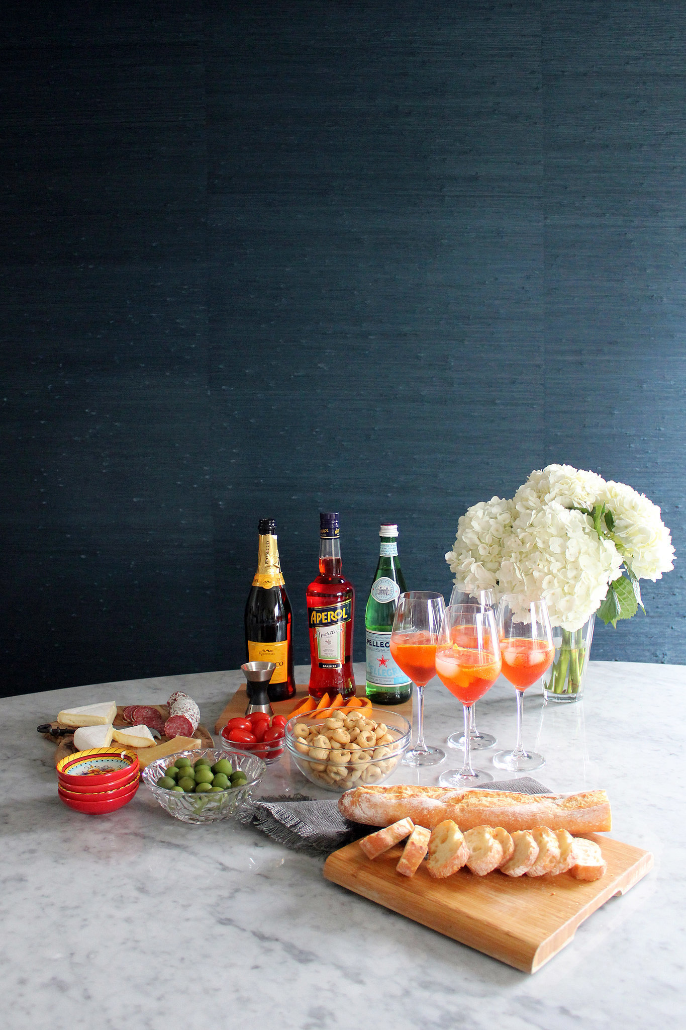 """Aperitivo time! One of Annie's favorite things to serve is a predinner drink, along with light snacks. Her go-to is Aperol Spritz, a bright, light drink that tastes just as great as it looks. Annie first tasted it when she and her husband were in Portofino, Italy, for their honeymoon. They asked their server for something that the locals drink, and as soon as she tasted it, she thought, """"This is Summer in a glass."""""""