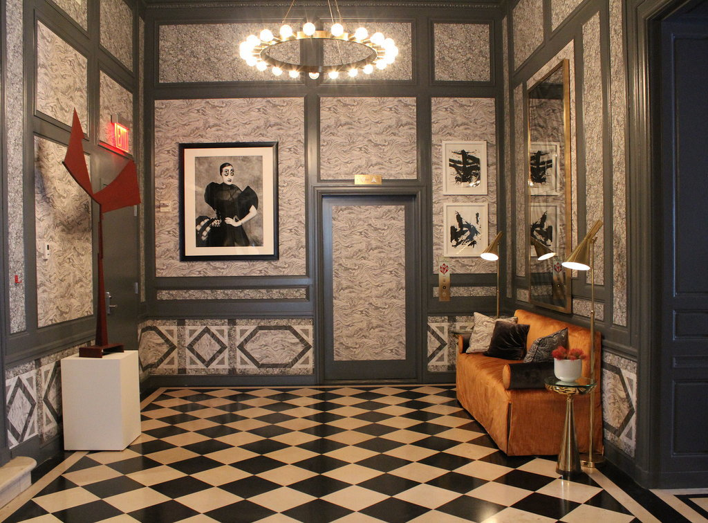 Marble papers were inserted into the wall panels to create an Italian palazzo feel, and the original checkerboard floor only enhances the effect.  Photo: Angela Elias