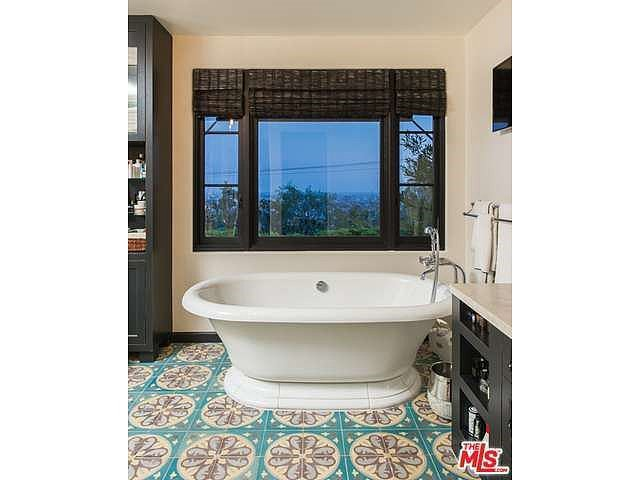 The beautifully tiled floor and soaking tub are the stars of this bathroom. Source: Coldwell Banker