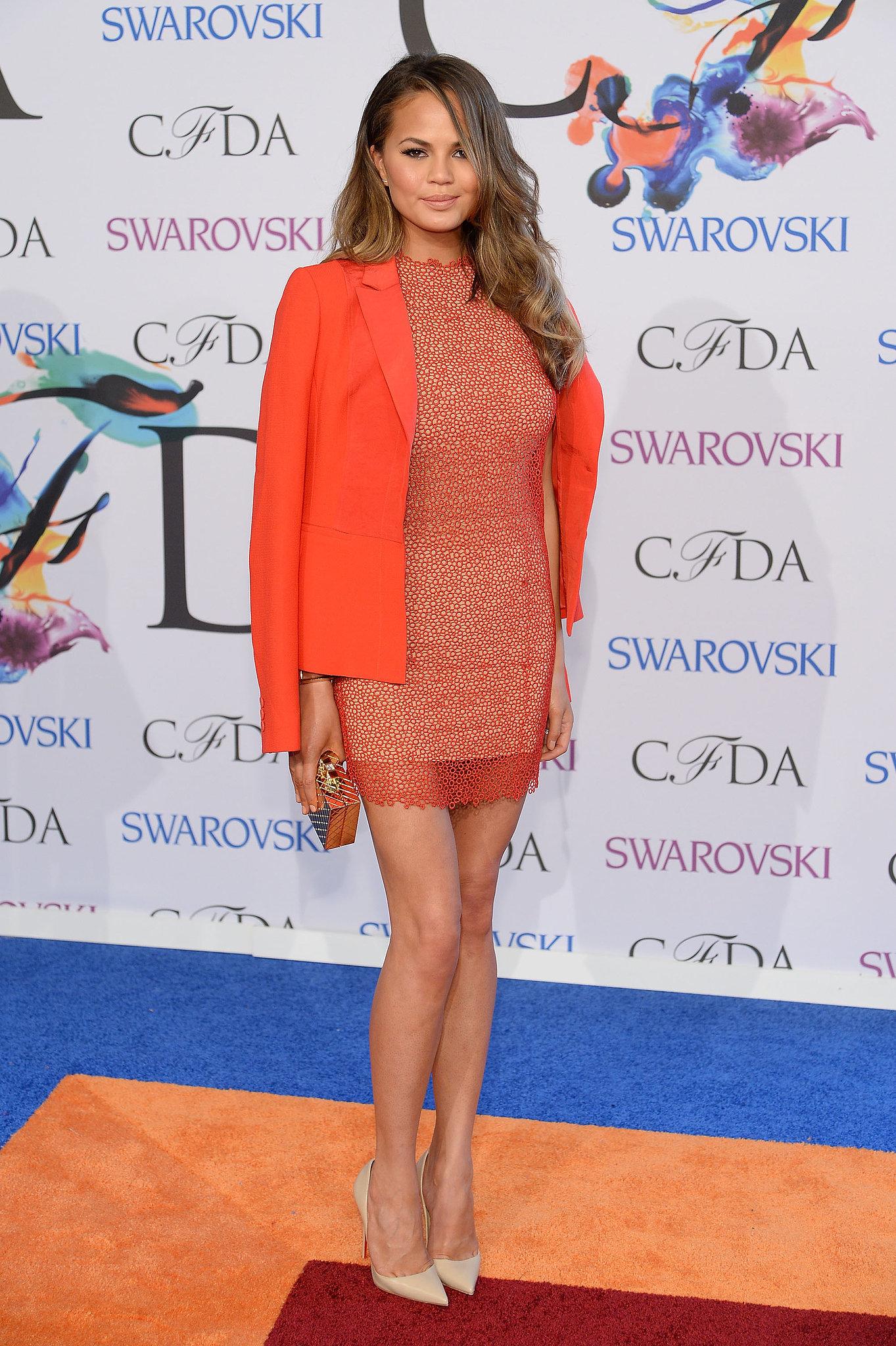 Chrissy Teigen wore an orange Rachel Roy ensemble.