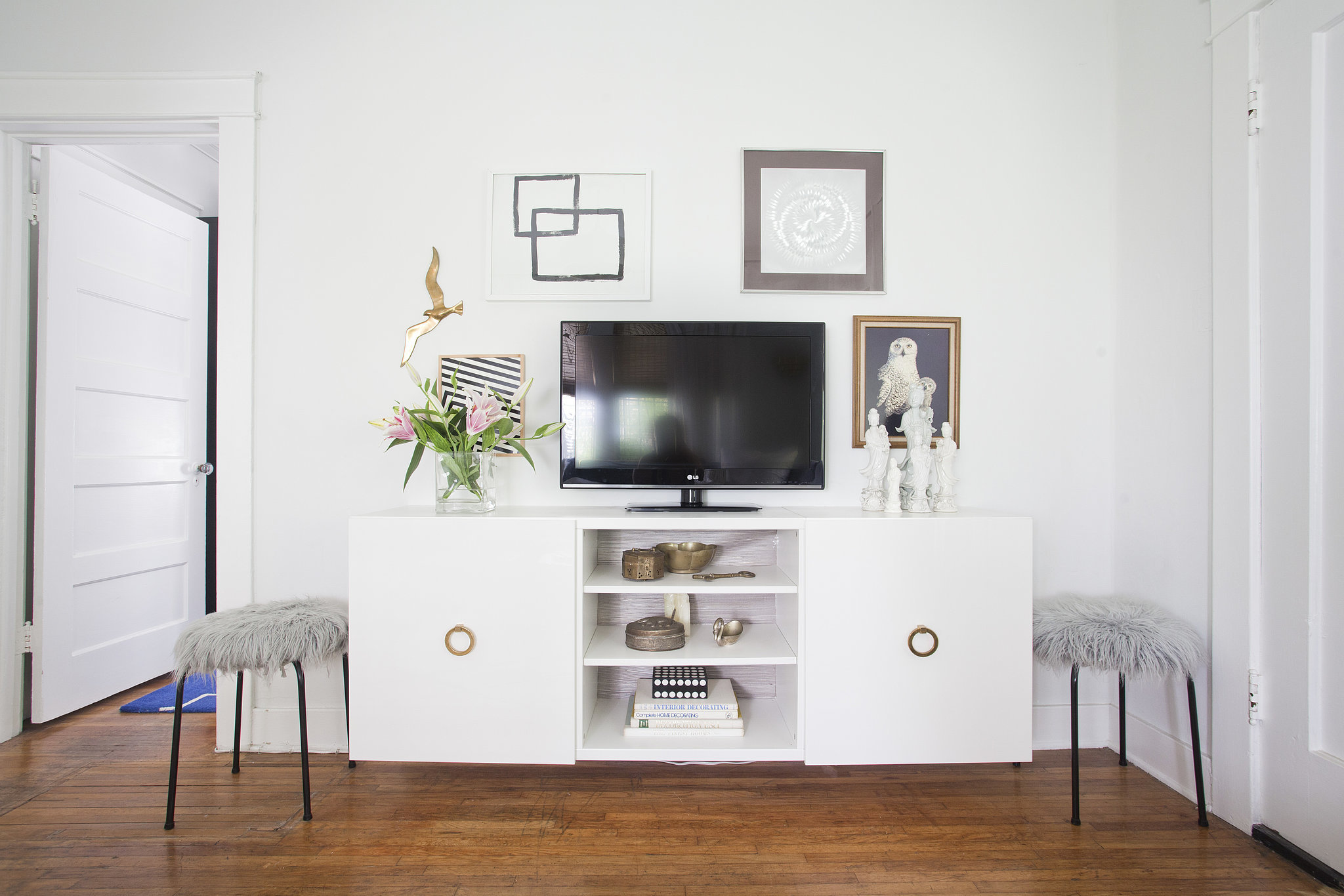 No, media units don't need to be black and boring. For a midcentury vibe, update your console with gold pulls and style a gallery wall with modern art and silver frames. Source:  Bethany Nauert via Homepolish