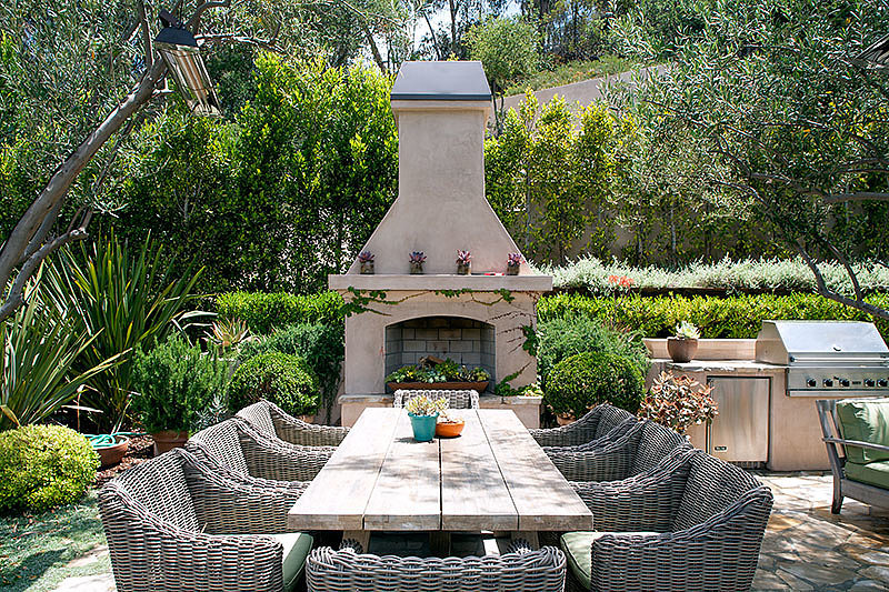 The custom fireplace and grill are perfect for outdoor entertaining.  Source: David Offer Fine Homes