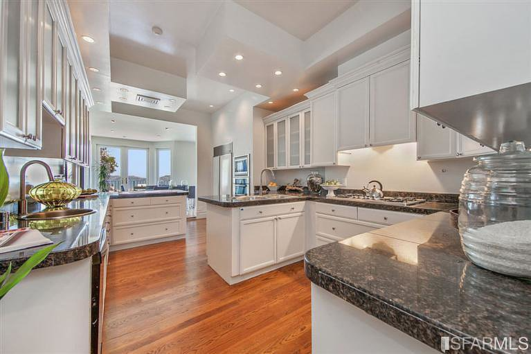 The kitchen is simple yet stunning with white cabinetry and stone countertops.  Source: Coldwell Banker