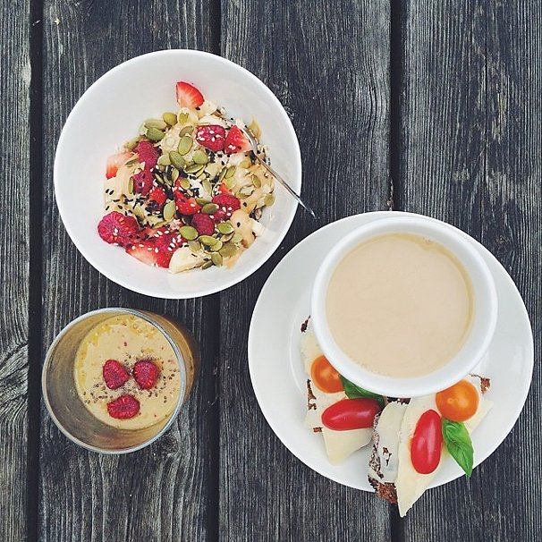 A breakfast that has us envious: mango and nectarine smoothie, oats with peanut butter and berries, and danish rye bread with cheese and tomato. Let's not forget the caffeine boost, either!