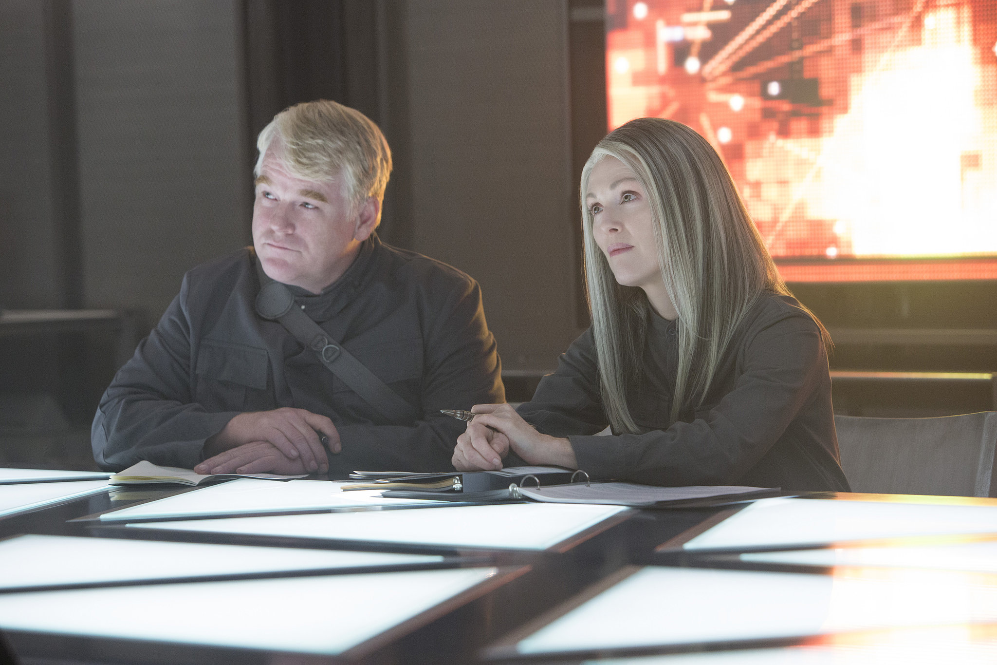 Philip Seymour Hoffman as Plutarch Heavensbee and Moore.