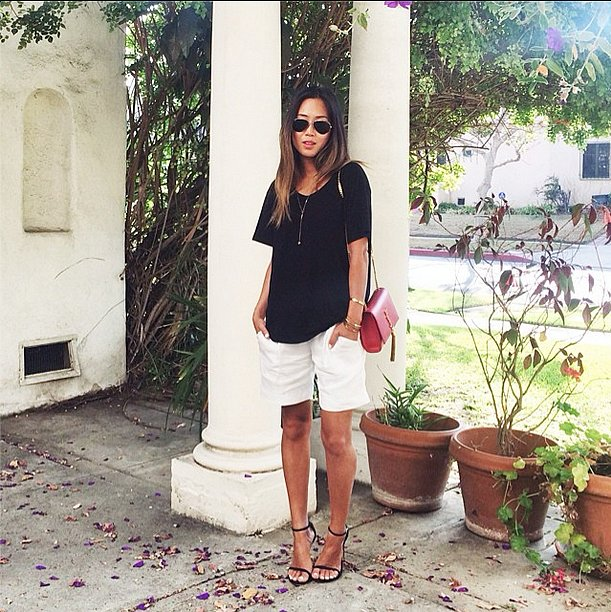 A simple, lived-in crew-neck t-shirt gets a major upgrade when paired with sleek accoutrements. Long shorts, strappy sandals, and a dainty statement chain up the fancy factor. Source: Instagram user songofstyle