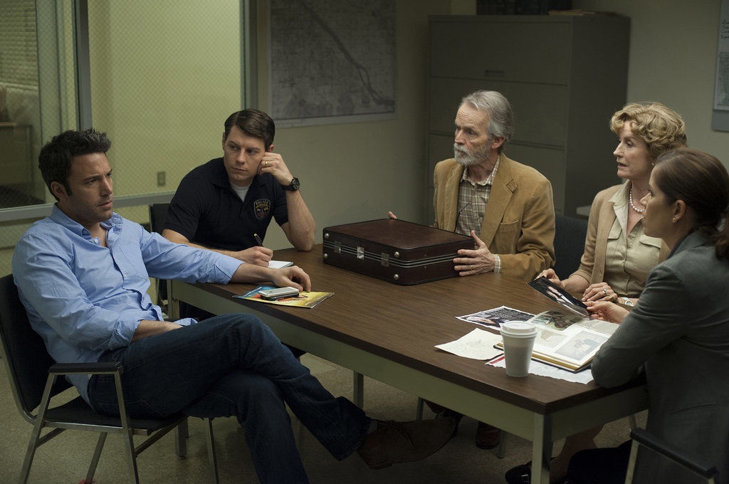 Nick confers with Detective Gilpin (Patrick Fugit) and Amy's parents (David Clennon and Lisa Banes).
