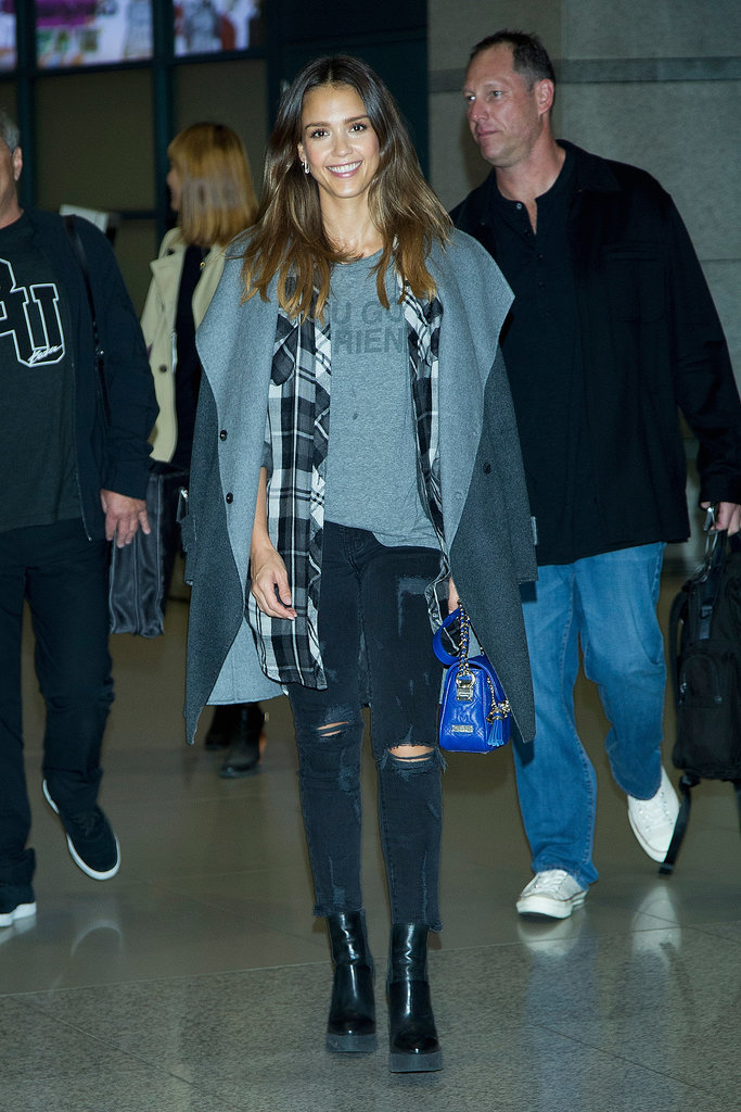 Jessica Alba layered up for her flight but didn't hide her cool-girl tee, plaid, or bright bag.